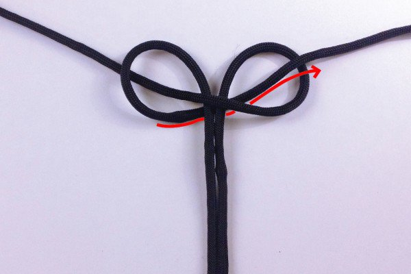 Take the left strand and pull it under the center pieces and up and over the right loop.
