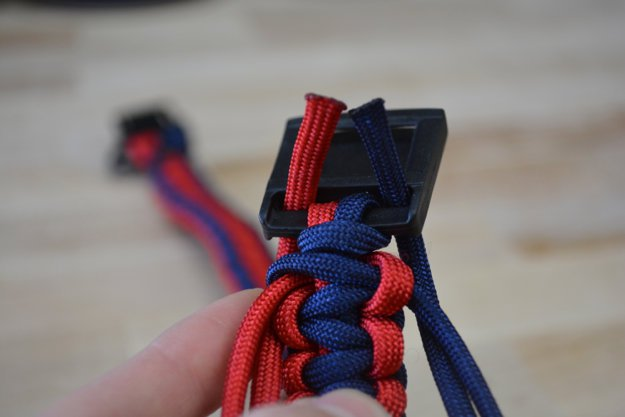 Turn the collar around and run the ends through the slot | Learn To Make A Paracord Dog Collar | Instructions