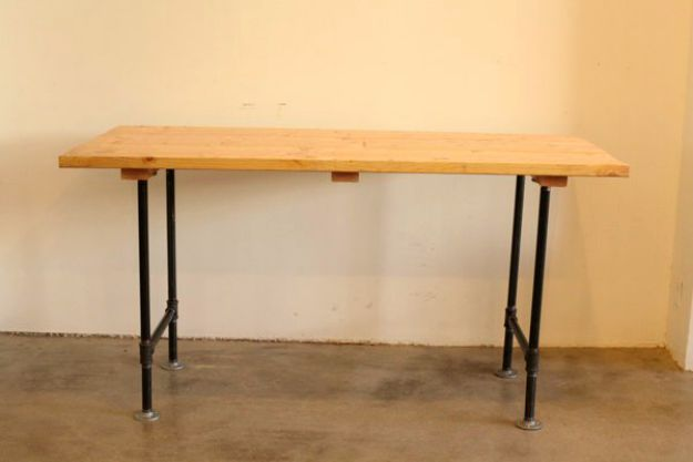 Four flanges are screwed down to the table | DIY Pipe Leg Table | Workbench Plans And Rustic Furniture Tutorial