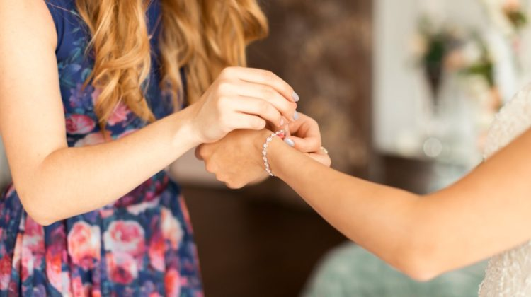 bridesmaids help to attach a bracelet with pearls to the bride | Easy Friendship Bracelets For Beginners To DIY | easy friendship bracelets for beginners | how to make easy friendship bracelets | Featured