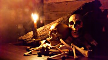 Candle lighting of skulls and bones pile with candle on wooden floor and old dirty wall | DIY Halloween Skull And Bones For Decorations | Featured