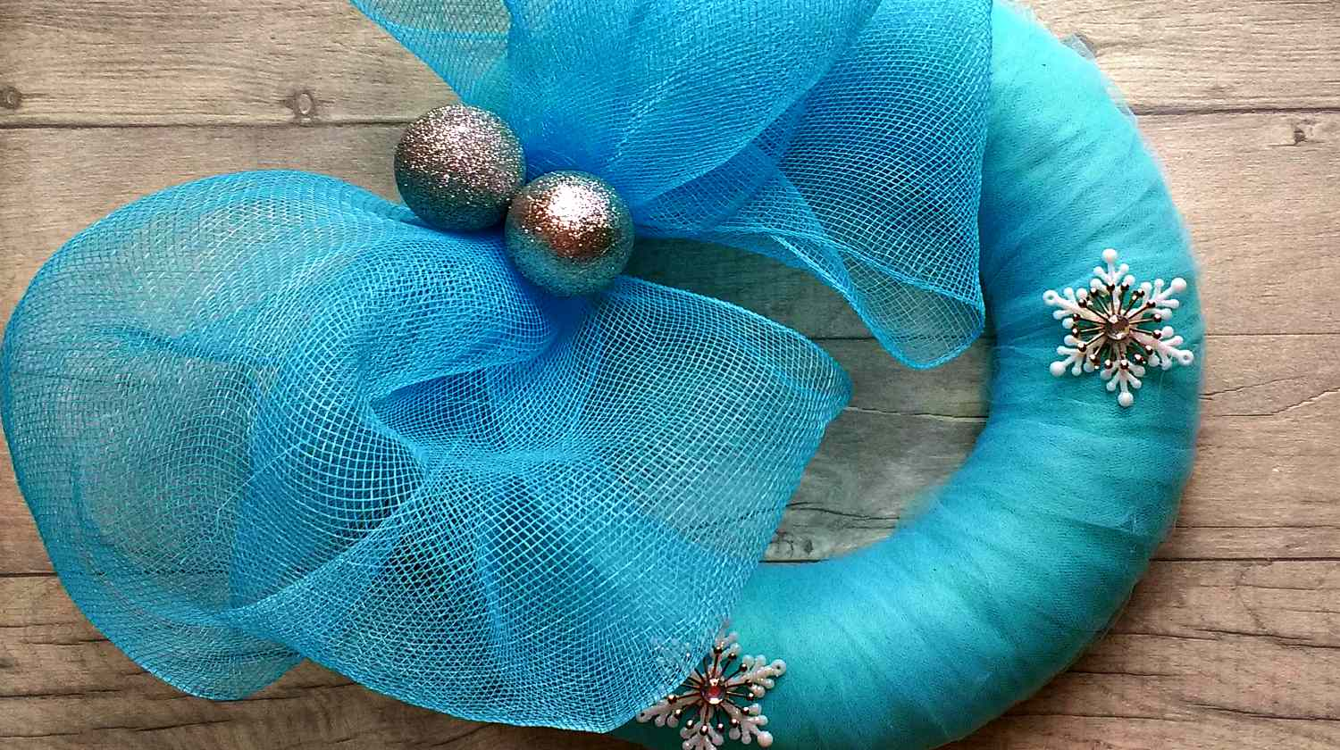Blue christmas wreath with silver baubles and stars on wooden surface | Mesh Wreath Project: DIY Mesh Wreath Ideas For All Seasons | Featured