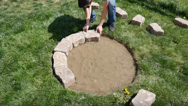 Start laying the first layer of bricks | Enjoy Your Cool Nights Outdoors With A DIY Stone Fire Pit