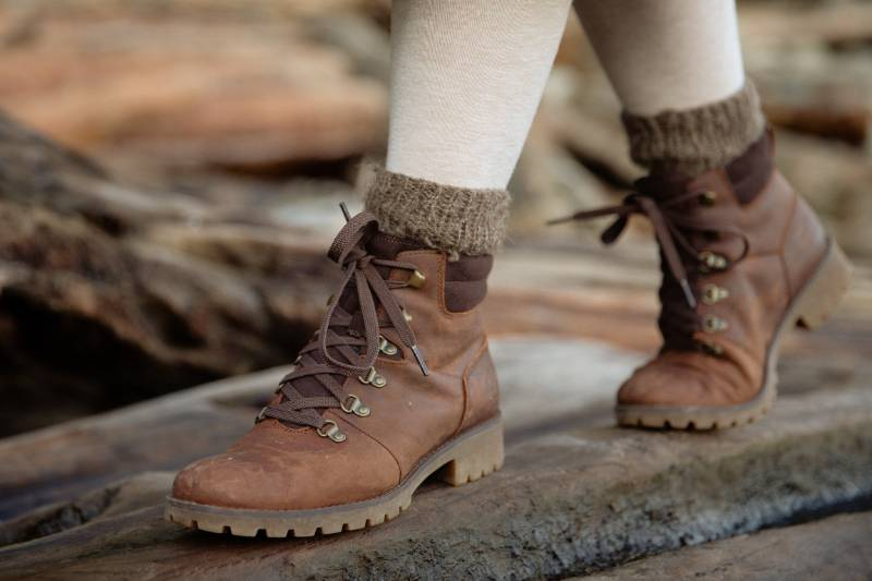 crop-person-in-autumn-boots-walking-on-wet-wooden-logs | boot cuffs