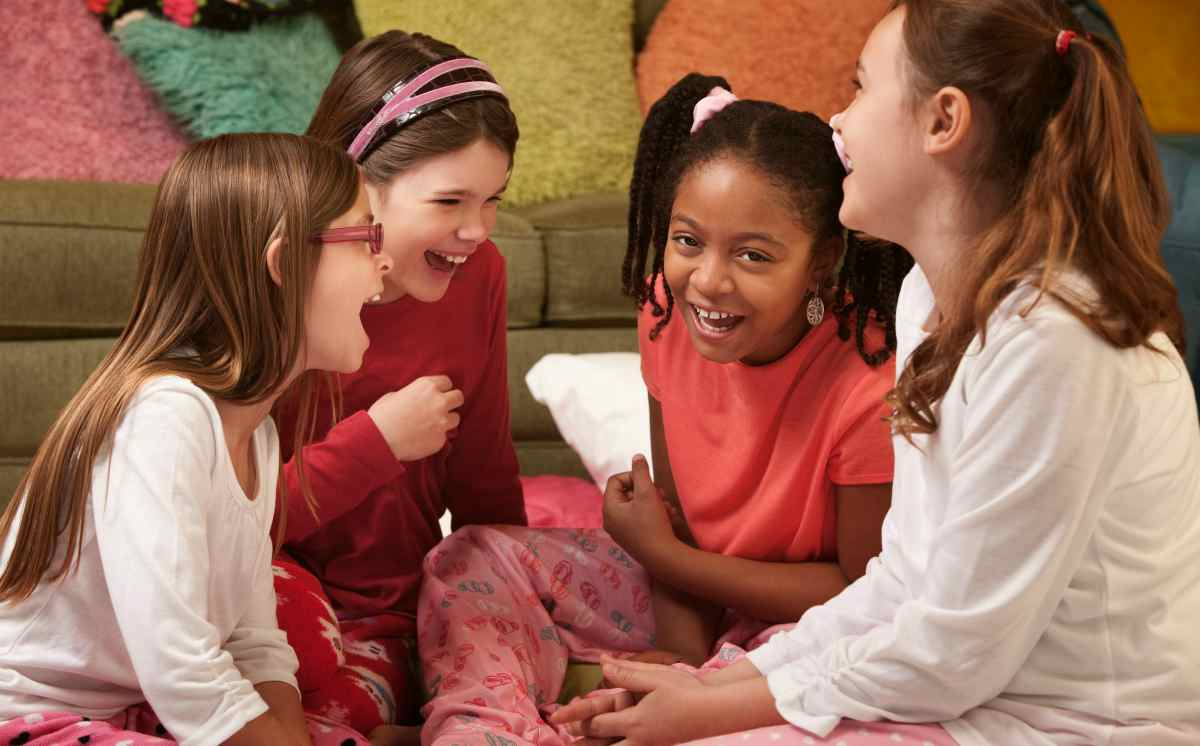 little girls in pajamas laughing on a sleepover | The Best Kids' Party Ideas For All Occasion