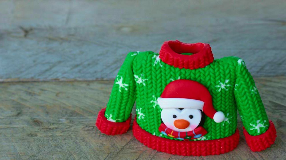 Green and red resin sweater with a penguin wearing Santa hat on it sitting on a natural wood background with writing space | Our DIY Christmas Ideas Roundup