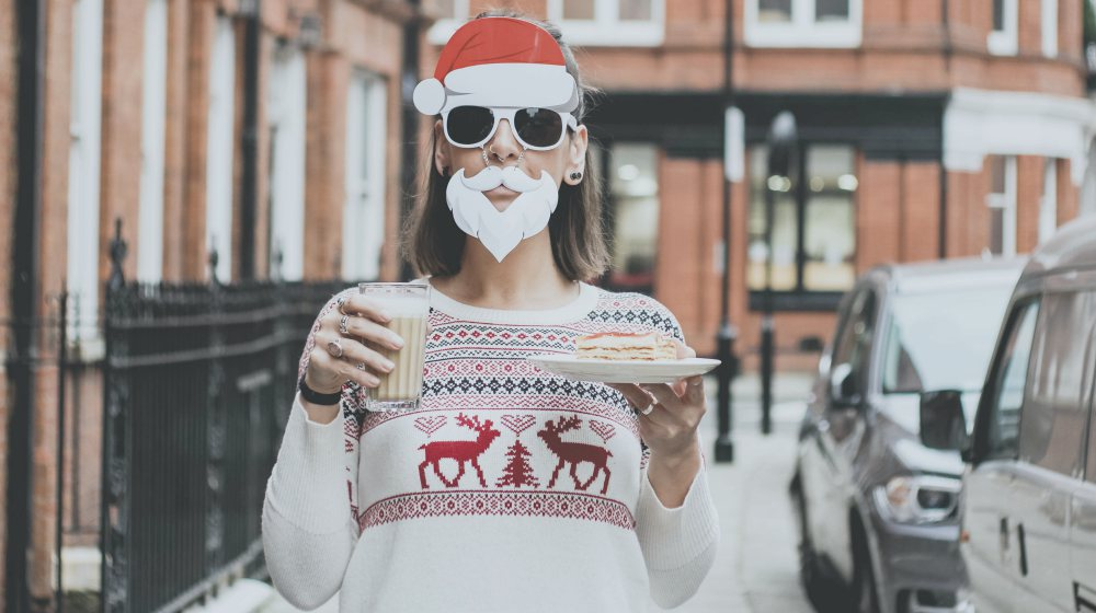 woman wearing an ugly Christmas sweater with mask santa hat and beard holding drink and slice of cake in the street | Christmas Sweater Ideas You Can DIY On A Budget | make your own christmas sweater online | Featured