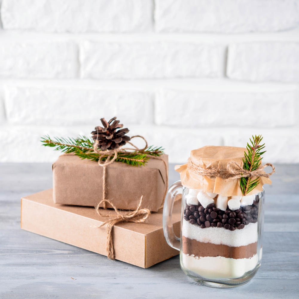 Hot chocolate mix in mason jar and rustic gift boxes on gray table and white brick wall | Make Hot Chocolate For The Holidays |