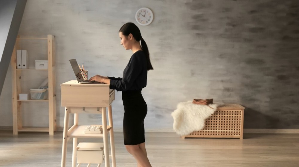 Asian woman typing on laptop at stand-up workplace | Build Your Own DIY Standing Desk For Your Home Office | Featured