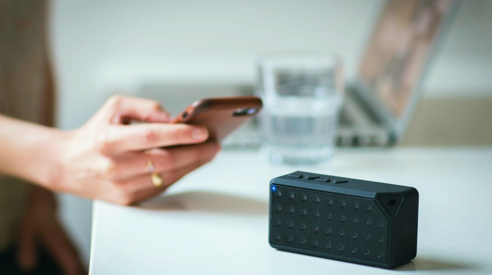 Person Holding Iphone Beside Black Portable Speaker | Create A New DIY Bluetooth Speaker From An Old Laptop | Featured