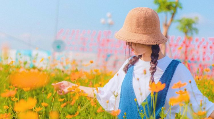 girl in flower field | DIY Sun Hat Ideas That Will Keep You Cool This Summer | hats that keep you cool in the summer | featured